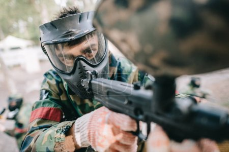Photo for Selective focus of male paintball player in goggle mask and camouflage aiming by paintball gun outdoors - Royalty Free Image