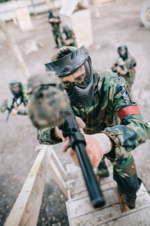 high angle view of male paintball player aiming by marker gun and running on staircase while his team standing behind outdoors