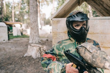serious female paintballer in protective mask and camouflage uniform standing with paintball gun outdoors
