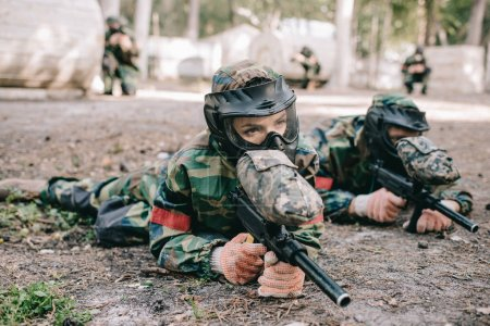 serious female paintball player in goggle mask and camouflage with marker gun crawling on ground near teammate outdoors