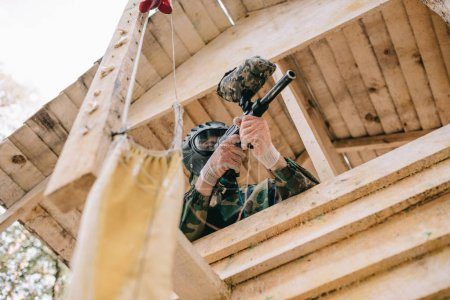 low angle view of paintball player in goggle mask and camouflage aiming by paintball gun on wooden tower outdoors