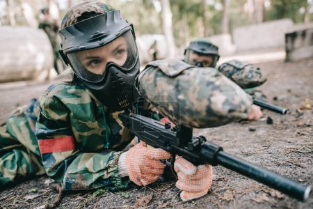 female paintball player in goggle mask and camouflage with marker gun crawling on ground outdoors