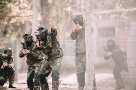 Photo for Paintball player in camouflage uniform pointing by hand to his team with markers guns outdoors - Royalty Free Image