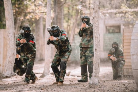 paintball team in uniform and protective masks running and aiming by paintball guns outdoors