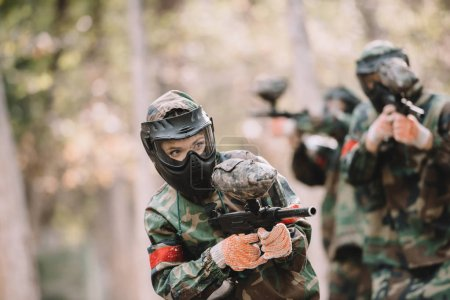 female paintballer in goggle mask and camouflage shooting by marker gun while her team running behind outdoors