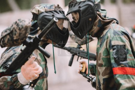 side view of male paintballers in protective masks and camouflage standing face to face outdoors