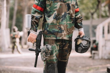 cropped image of paintball player holding marker gun and goggle mask covered by paintball splash outdoors