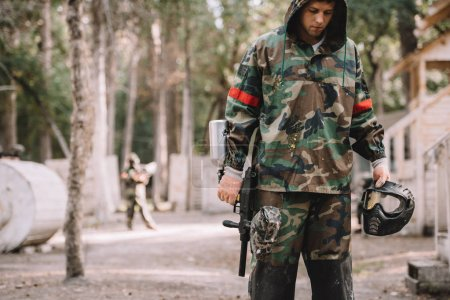 young male paintball player in camouflage covered by paintball splash outdoors