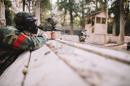 Photo for Selective focus of paintball player in protective mask and camouflage aiming by marker gun outdoors - Royalty Free Image