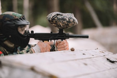 side view of male paintball player in goggle mask and camouflage aiming by paintball gun outdoors