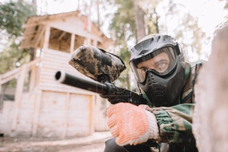serious male paintball player in goggle mask and camouflage aiming by paintball gun outdoors