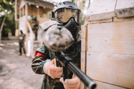 selective focus of male paintballer in goggle mask covered by paintball splash aiming by marker gun outdoors
