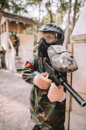 focused male paintballer in goggle mask covered by paintball splash aiming by marker gun outdoors