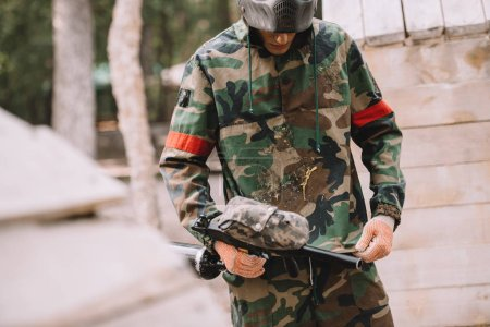 male paintball player with marker gun looking at camouflage covered by paintball splash outdoors