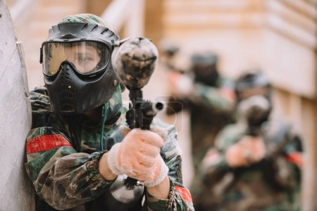male paintballer in goggle mask covered by paintball splash aiming by marker gun outdoors