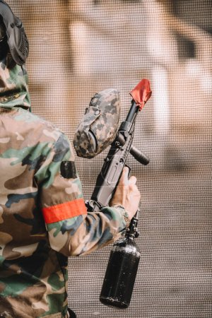 partial view of male paintball player in goggle mask and camouflage holding paintball gun outdoors