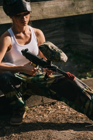 concentrated female paintballer in white singlet and goggle mask loading paintball gun outdoors
