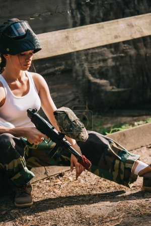 female paintballer in white singlet and goggle mask holding paintball gun outdoors
