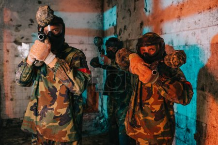 paintball team in uniform and protective masks aiming by paintball guns in abandoned building