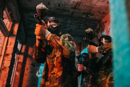 low angle view of paintball team in uniform and protective masks aiming by paintball guns in abandoned building