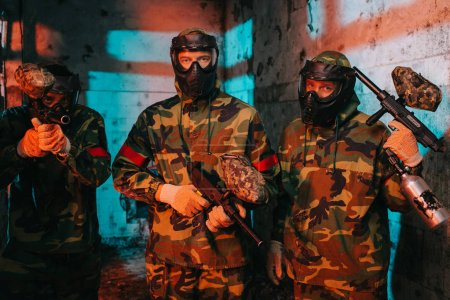 portrait of paintball team in uniform and protective masks with paintball guns in abandoned building