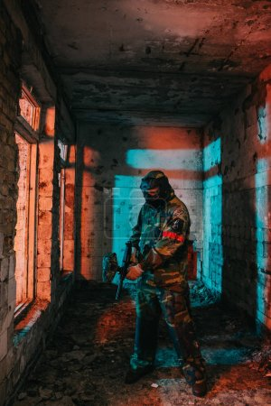 male paintball player in goggle mask and camouflage loading paintball gun in abandoned building