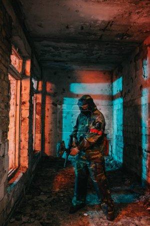 Photo pour Joueur de paintball masculin en masque de masque et camouflage chargement pistolet de paintball dans le bâtiment abandonné - image libre de droit
