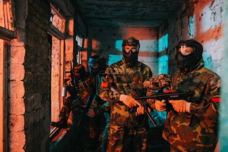 paintball team in uniform and protective masks standing with paintball guns in abandoned building