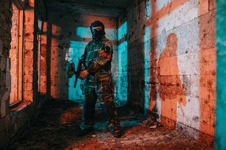 Photo pour Joueur de paintball mâle confiant en lunettes masque et camouflage tenant le pistolet de paintball dans le bâtiment abandonné - image libre de droit