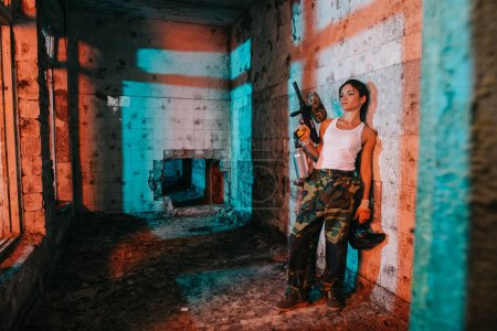 young female paintballer in camouflage and white singlet holding paintball gun and goggle mask in abandoned building