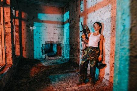 Photo pour Jeune femelle paintballer en camouflage et blanc singulet tenant paintball pistolet et goggle masque dans bâtiment abandonné - image libre de droit
