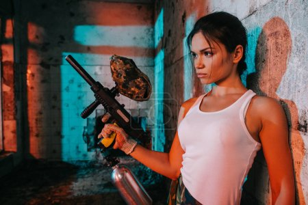 beautiful young female paintballer in camouflage and white singlet holding marker gun in abandoned building