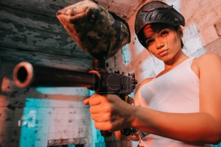 attractive female paintballer in camouflage and goggle mask above head aiming by paintball gun in abandoned building