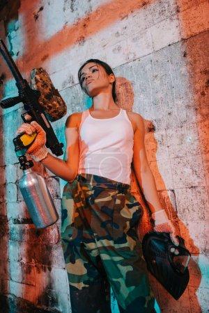Foto de Mujer paintballer en camiseta de camuflaje blanco y negro con marcador pistola y gafas de máscara en edificio abandonado - Imagen libre de derechos