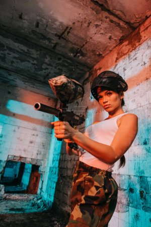 attractive young female paintballer in goggle mask above head aiming by paintball marker in abandoned building