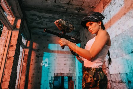 low angle view of young female paintballer in camouflage and white singlet aiming by marker gun in abandoned building
