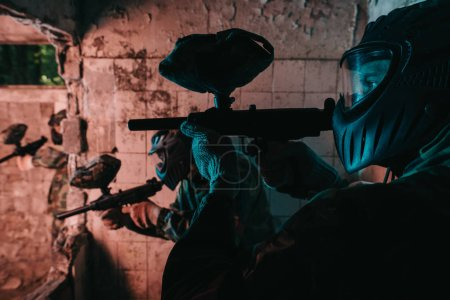 close up view of paintball team in uniform and protective masks playing paintball with marker guns in abandoned building