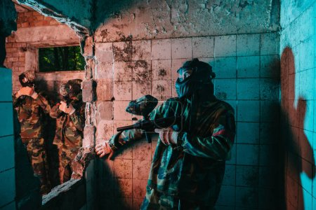 male paintball player in goggle mask and camouflage uniform hiding behind wall while other team is standing near in abandoned building