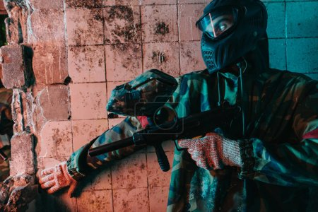 male paintball player in camouflage and goggle mask hiding behind wall and holding marker gun in abandoned building