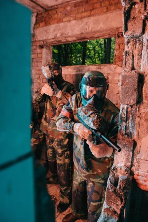 paintball team in uniform and protective masks playing standing with paintball guns in abandoned building