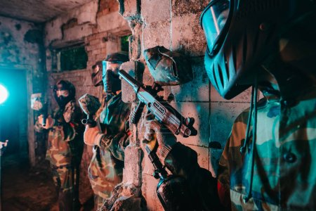 partial view of male paintball player in goggle mask and camouflage uniform hiding behind wall and aiming marker gun at player of other team in abandoned building