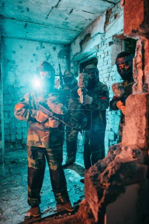 paintball team in uniform and protective masks with paintball guns in abandoned building