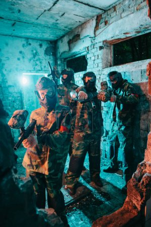paintball team in uniform and protective masks aiming by paintball guns at camera in abandoned building