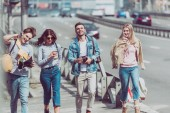 young friends with map and backpacks traveling together in new city