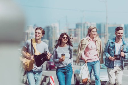 smiling friends with map and backpacks traveling together in new city