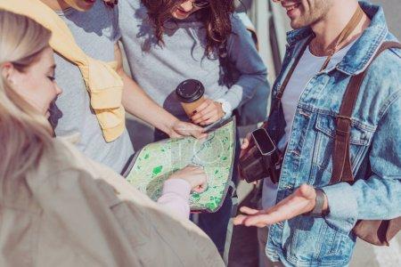 Photo pour Vue partielle de jeunes amis à la recherche de la destination sur la carte tout en voyageant ensemble - image libre de droit
