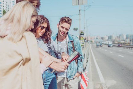 Photo for Partial view of young friends looking for destination on map while traveling together - Royalty Free Image