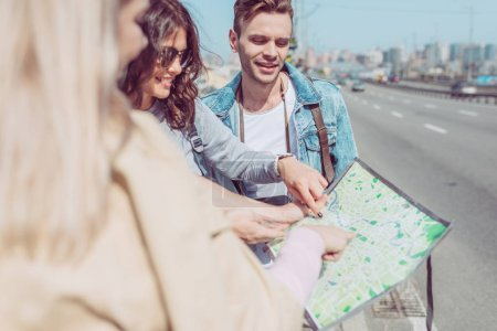 partial view of tourists looking for destination on map during trip