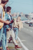 woman hitchhiking on road while friends standing behind