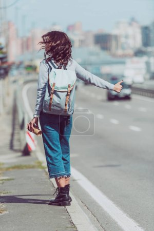 rear view of woman with backpack and coffee to go hitchhiking at road